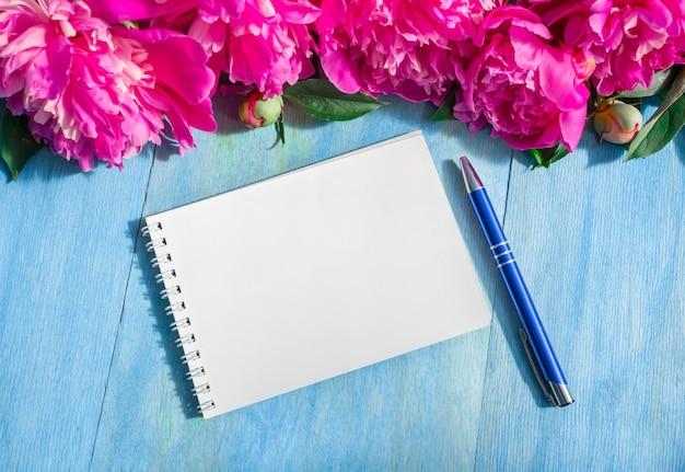 Piękne piones, długopis, notatnik na niebieskim tle. skopiuj miejsce