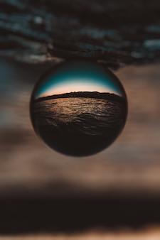 Piękne pionowe zbliżenie strzał szklanej kuli z odbiciem zapierającego dech w piersiach zachodu słońca