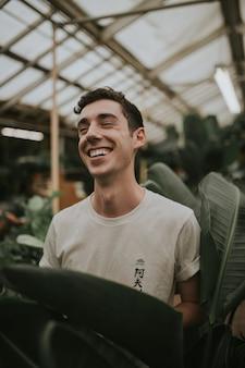 Piękne pionowe zdjęcie młodego mężczyzny w szklarni w otoczeniu liści