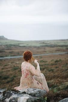 Piękne pionowe zdjęcie rudej suki o czystej białej skórze w atrakcyjnej różowej sukni