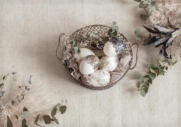 Piękne pisanki w koszyczku ozdobionym suszonymi kwiatami. koncepcja wesołych świąt.