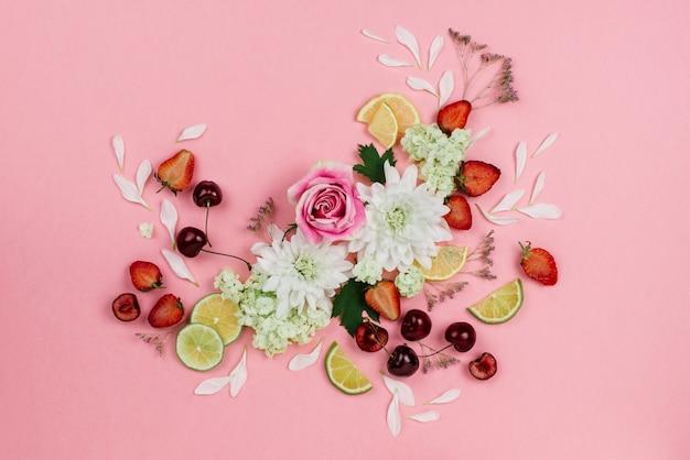 Piękne płaskie ułożenie różnych owoców, jagód i kwiatów na różowo