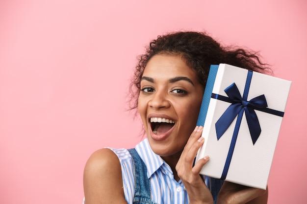 Piękne podekscytowana młoda kobieta afryki, trzymając pudełko na różowo
