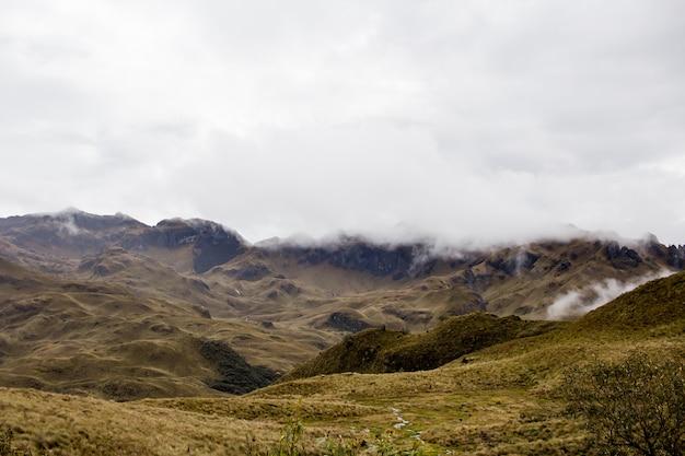 Piękne pole z niesamowitymi skalistymi górami i wzgórzami oraz niesamowitym pochmurnym niebem