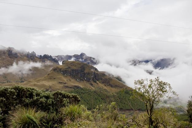 Piękne pole z niesamowitymi wzgórzami skalistych gór i niesamowitym pochmurnym niebem