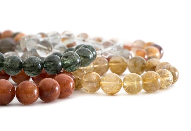 Piękne, półprzezroczyste, różne kolory rutilated quartz lub venus ™ perełka z włosia w bransoletkach na białym tle