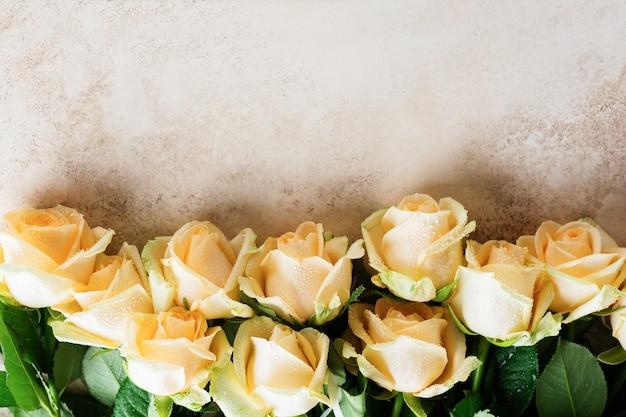Piękne pomarańczowe róże na jasnej betonowej powierzchni. kompozycja pozioma. tekst na gratulacje na walentynki lub wesele