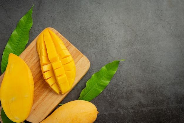 Piękne posiekane dojrzałe mango na ciemnej powierzchni drewnianej