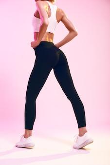 Piękne pośladki widok z tyłu sportowej szczupłej kobiety z idealnym ciałem w sportowej odzieży stojącej naprzeciw