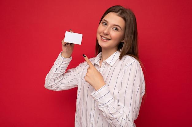 Piękne pozytywne uśmiechnięte młode ciemne blond kobieta ubrana w białą bluzkę na białym tle na czerwonym tle trzymając kartę kredytową patrząc na kamery, wskazując palcem na plastikową kartę zbliżeniową.