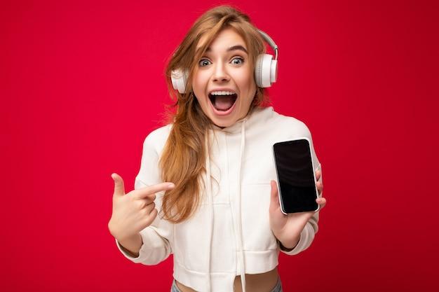 Piękne pozytywne zdumiony młoda kobieta ubrana w stylowy strój dorywczo na białym tle na ścianie w tle