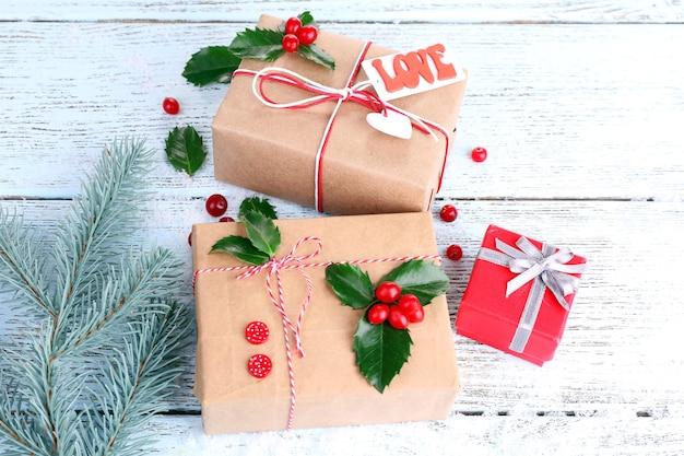 Piękne prezenty cristmas z ostrokrzewem europejskim (ilex aquifolium) na drewnianym tle