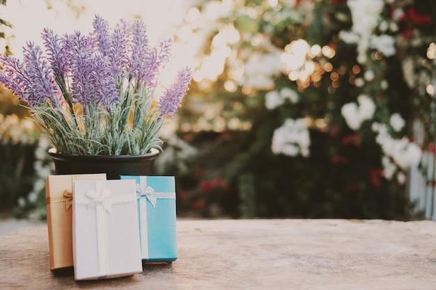 Piękne prezenty ułożone na drewnianym stole z ładną lawendą.