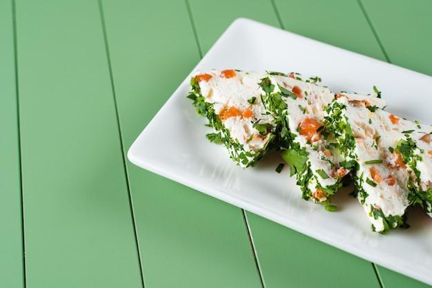Piękne przekąski z miękkiego serka śmietankowego na białym talerzu na zielonym stole. przekąski z twarogu z łososiem i ziołami.