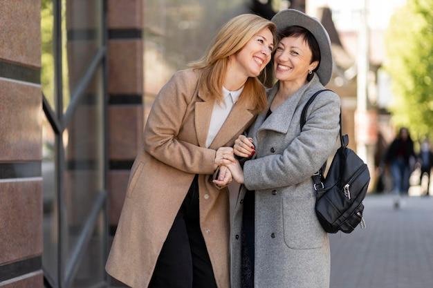 Piękne przyjaciółki w średnim wieku spędzające razem czas w mieście