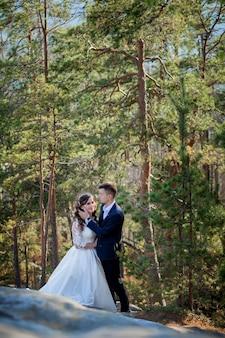 Piękne przytulanie nowożeńców. stylowa panna młoda i piękna panna młoda stoją na klifie. portret ślubny. rodzinne zdjęcie