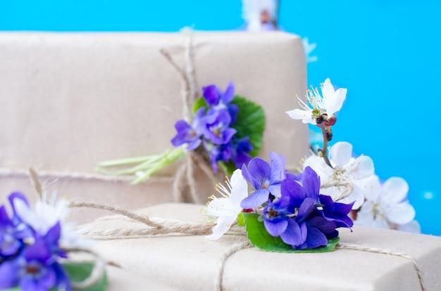 Piękne pudełka na prezenty owinięte prostym brązowym papierem rzemieślniczym ozdobione żywymi kwiatami fioletu