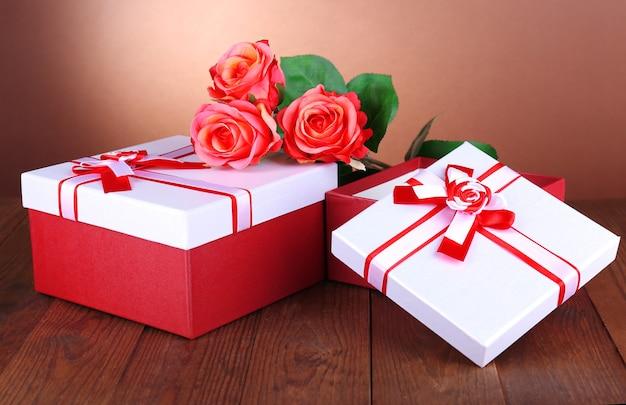 Piękne pudełka na prezenty z kwiatami na stole na brązowym tle