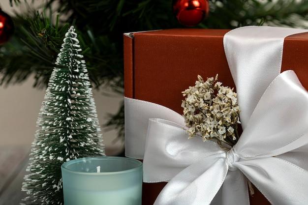 Piękne pudełko na prezenty z białą wstążką i białymi kwiatami pod choinką
