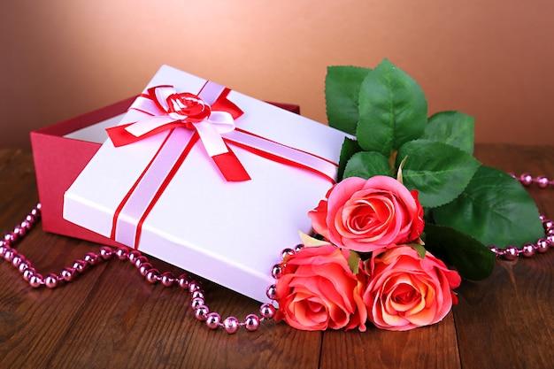 Piękne pudełko z kwiatami na stole na brązowym tle
