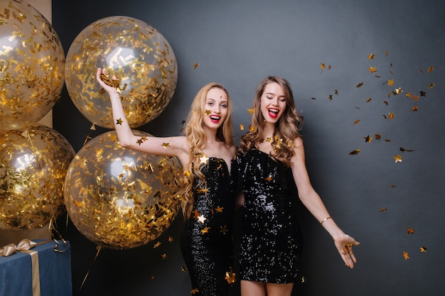 Piękne radosne młode kobiety w czarnych luksusowych sukienkach, bawiąc się złotymi błyskotkami. świętujemy wspaniałą imprezę, nowy rok, wielkie balony, wszystkiego najlepszego z okazji urodzin, uśmiechnięty, wesoły nastrój