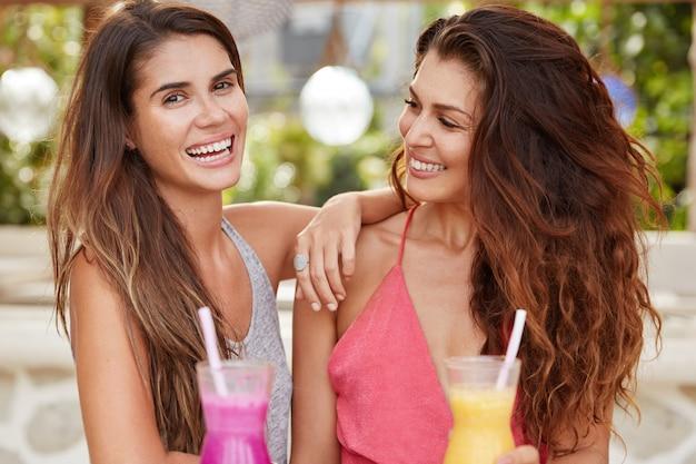Piękne, radosne, radosne kobiety z pozytywnymi minami obejmują się, spędzają wolny czas w kawiarni na tarasie, piją razem świeży koktajl
