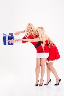 Piękne radosne siostry bliźniaczki w czerwonych strojach świętego mikołaja wygłupiają się z prezentami i śmieją się na białym tle