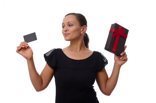 Piękne rasy mieszanej hiszpanie kobieta patrzy na plastikową kartę kredytową lub rabatową w dłoni i trzyma czarne pudełko z czerwoną wstążką w drugiej ręce . koncepcja czarnego piątku z kopią miejsca
