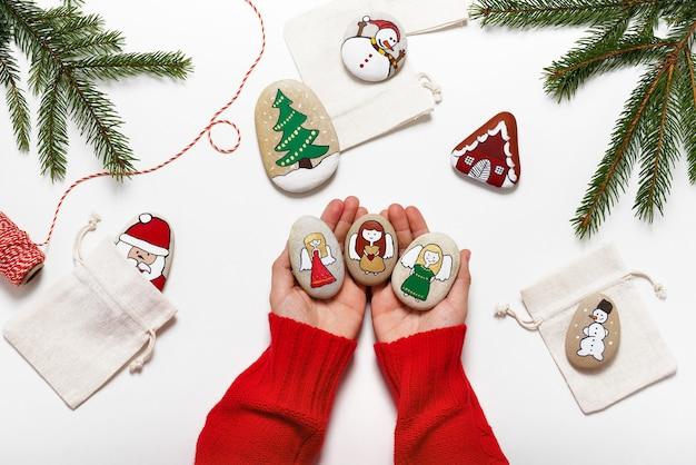 Piękne ręcznie malowane kamienie z motywem anioła trzymane w dłoniach. łatwa zabawa dla dzieci.