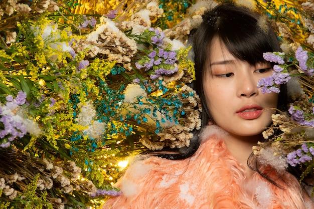 Piękne romantyczne młode azjatyckie kobiety w starej róży futra w różnorodność krzewów kwiatów stwarzających na tle flory świeżej i suszonej. inspiracja jesienno-zimowym śniegiem perfumy, koncept kosmetyków.
