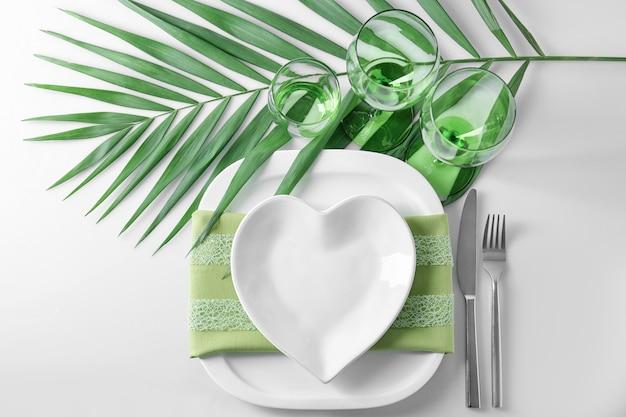 Piękne romantyczne nakrycie stołu z zielonym liściem