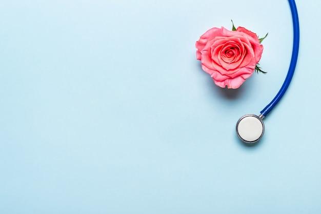 Piękne różane serce i stetoskop na niebieskim tle. dziękuję koncepcji dnia lekarza i pielęgniarki.