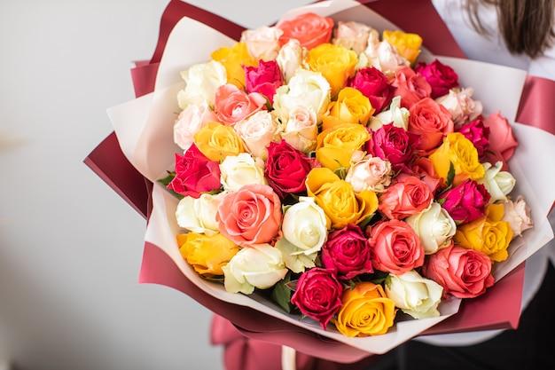 Piękne róże w rękach. wiosna, lato, kwiaty, kolorystyka. dostawa kwiatów