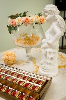 Piękne róże w szklanym wazonie z czekoladowymi cukierkami na uroczystość