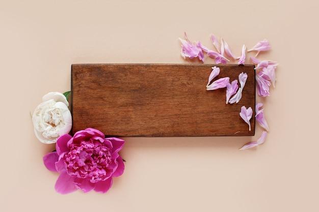 Piękne różowe i białe peonie na drewnianym tle
