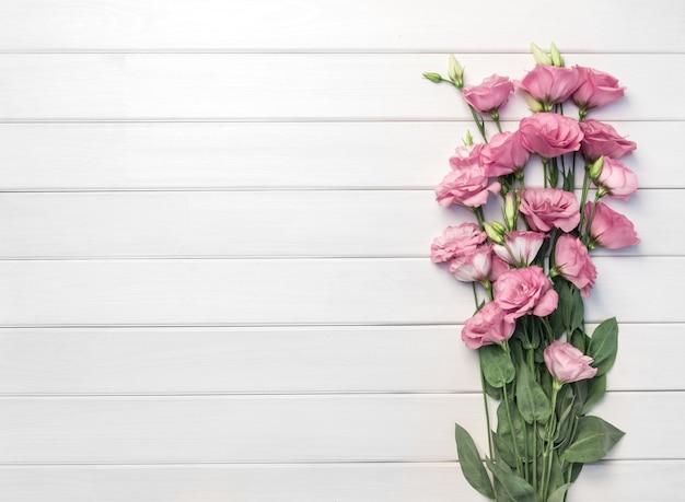 Piękne różowe kwiaty eustoma na białym drewnianym stole, widok z góry