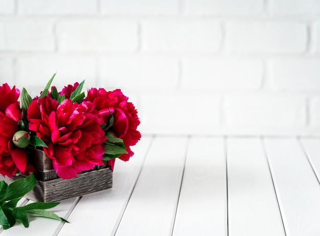 Piękne różowe kwiaty piwonii marsala w drewnianym pudełku na rustykalnym drewnianym stole z miejscem na tekst.