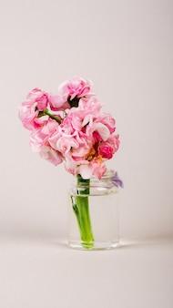 Piękne różowe kwiaty w butelce na jednolitym tle skopiuj przestrzeń pionową mobilną format...