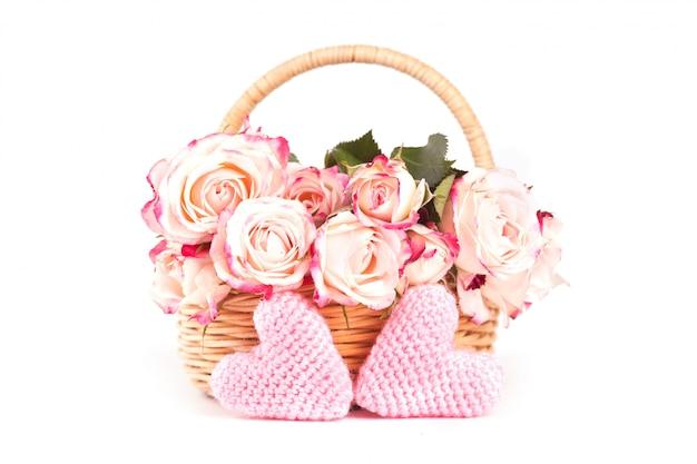 Piękne różowe róże w wiklinowym koszu i dwa dzianiny różowe serca na białym tle.