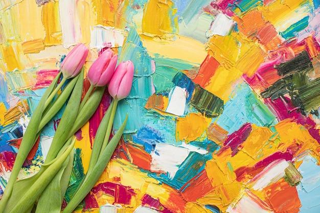 Piękne różowe tulipany na wielobarwnym tle papieru z miejsca na kopię. wiosna, lato, kwiaty, kolorystyka, dzień kobiet.