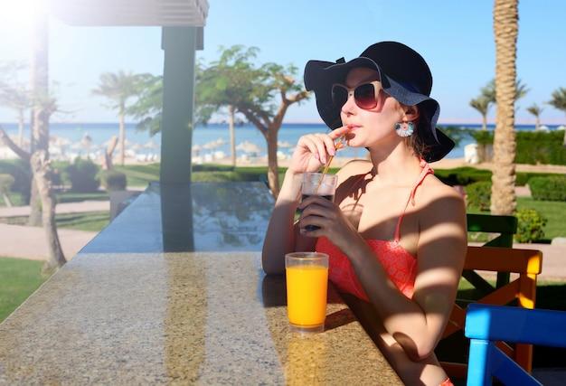 Piękne seksowne kobiety w bikini w barze na hawajskim barze na plaży. ciesząc się koktajlem alkoholowym na zewnątrz. uśmiechnięte szczęśliwe kaukaskie kobiety w kapeluszu na hawajskiej plaży.