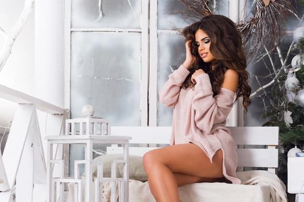 Piękne seksowne kobiety w delikatnym różowym swetrze o idealnym ciele, siedzące w pobliżu choinki