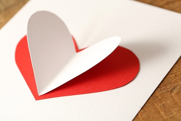 Piękne serce papierowe na białym papierze, zbliżenie