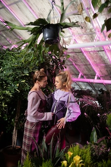 Piękne siostry. atrakcyjne stylowe kobiety patrzące na siebie stojąc w szklarni