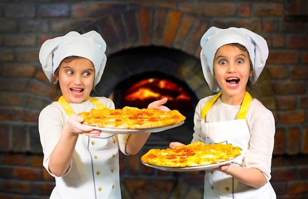 Piękne siostry bliźniaczki dziewczyny w kapeluszach kucharza, trzymając pizzę na kamiennym piecu