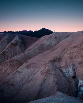 Piękne skaliste góry i wzgórza z niesamowitym zapierającym dech w piersiach gwiaździstym niebem