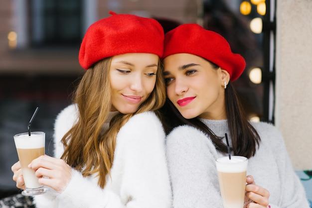 Piękne śliczne dziewczyny w czerwonych beretach trzymających kawę latte, kobiecą przyjaźń i pyszne śniadanie