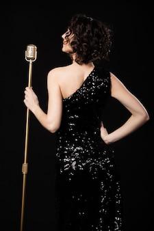 Piękne slim dziewczyna piosenkarka trzyma złoty vintage mikrofon