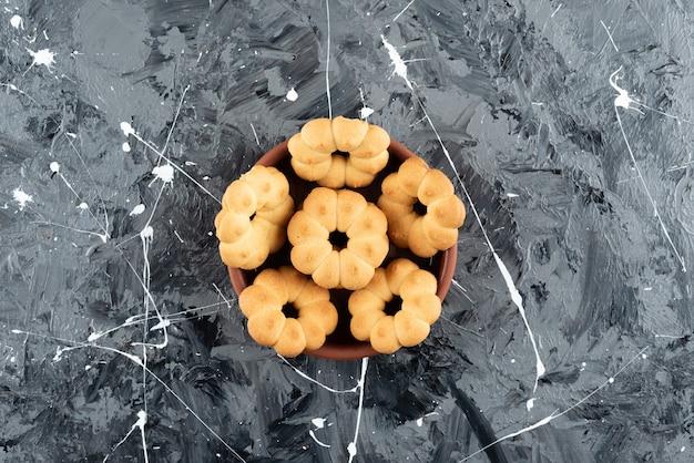 Piękne słodkie ciasteczka do herbaty w glinianej misce na marmurowym tle.