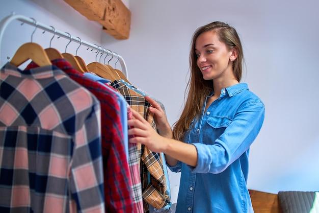 Piękne słodkie dorywczo uśmiechnięta szczęśliwa kobieta wybiera strój w swojej szafie
